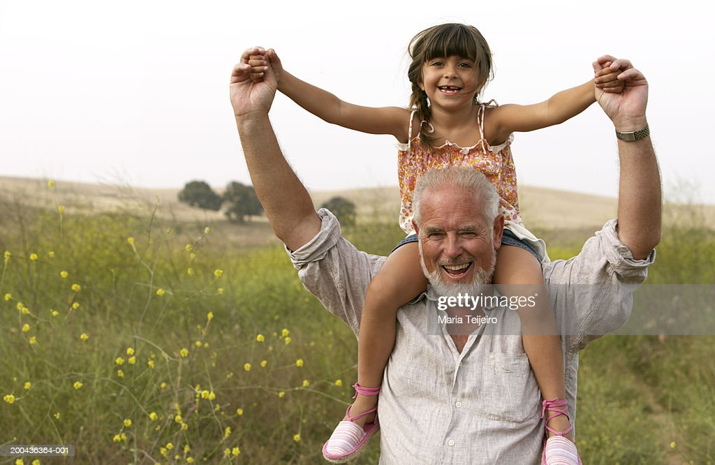 Girl (4-6) sitting on grandfather's shoulders, smiling, portrait : Stock Photo