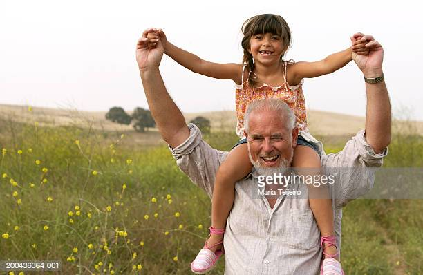 Girl (4-6) sitting on grandfather's shoulders, smiling, portrait