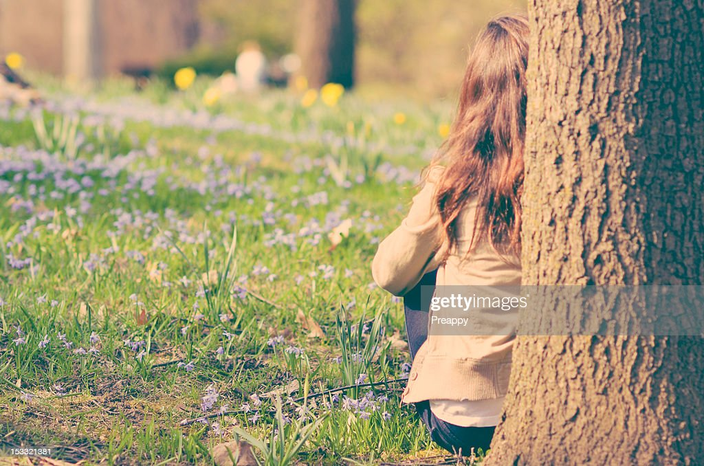 Girl sitting on grass leaning against  tree : Stock Photo