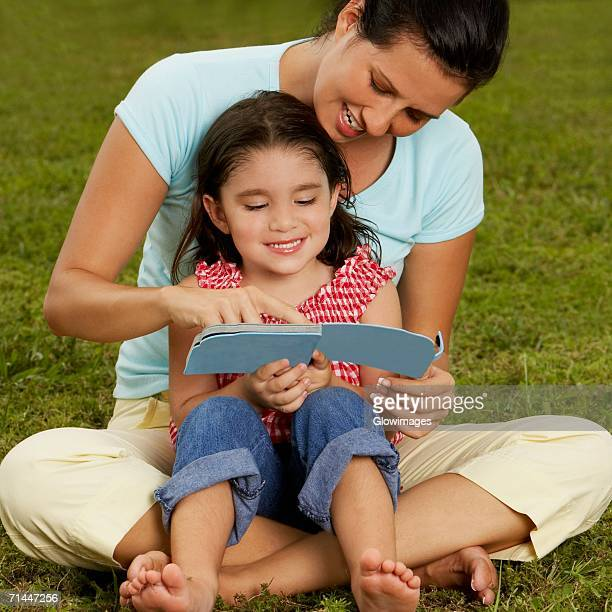 Girl sitting on her mother's lap and reading a book