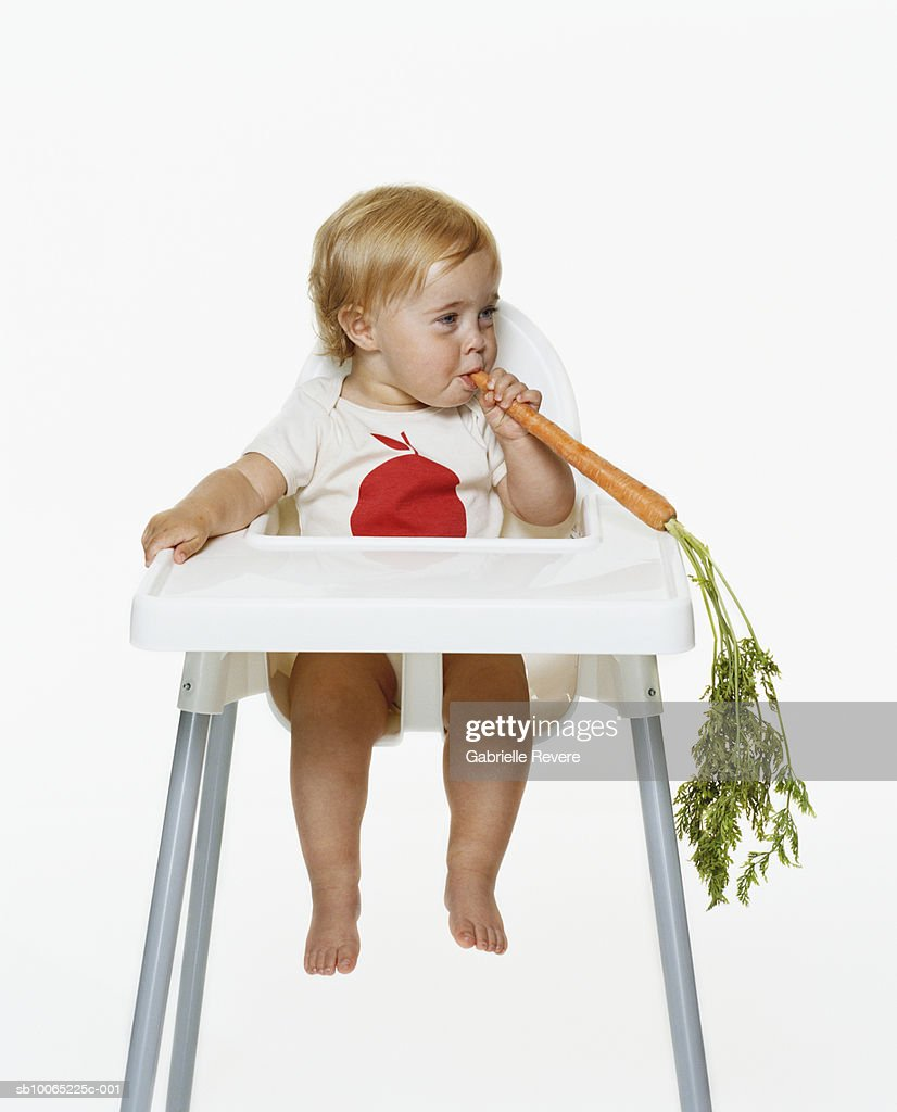 Girl (21-24 months) sitting on highchair eating carrot : Stock Photo