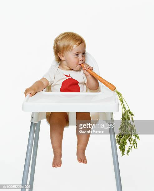 Girl (21-24 months) sitting on highchair eating carrot