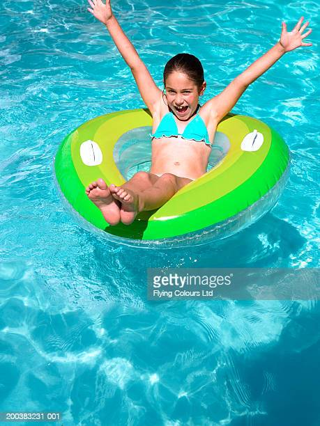 Girl (8-10) sitting on inflatable in swimming pool, arms raised