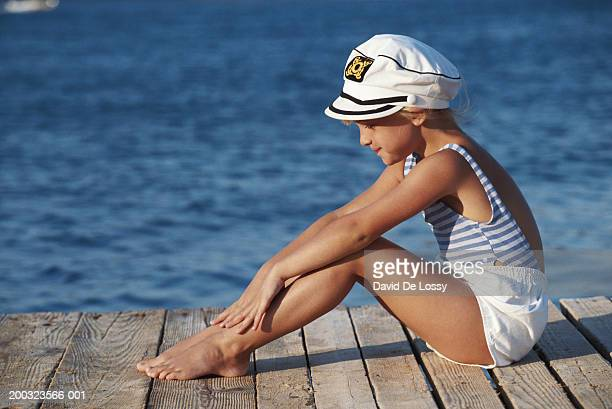 Girl (6-7) sitting on jetty, side view