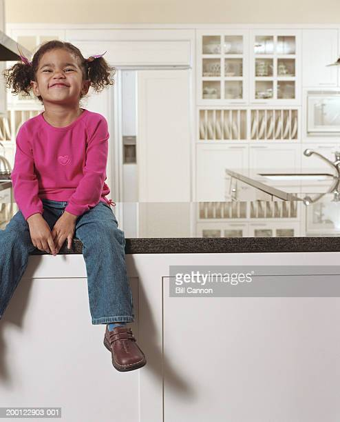 Girl (2-4) sitting on kitchen counter, smiling, portrait
