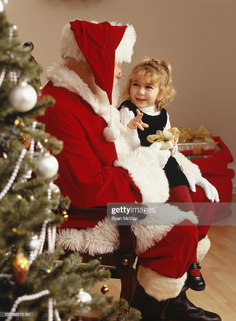 Girl (3-4) sitting on lap of Santa Claus by Christmas tree