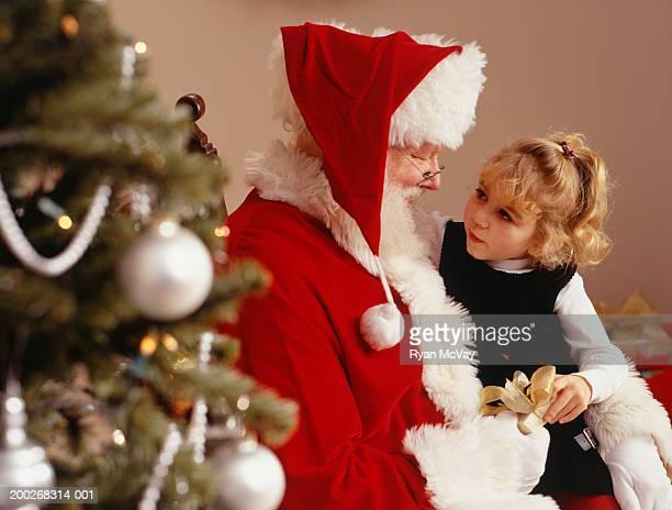 Girl (4-5) sitting on lap of Santa Claus