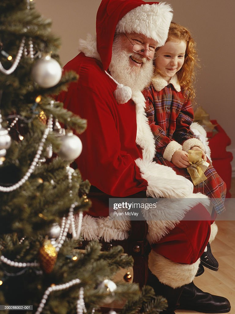 Girl (6-7) sitting on lap of Santa Claus, portrait