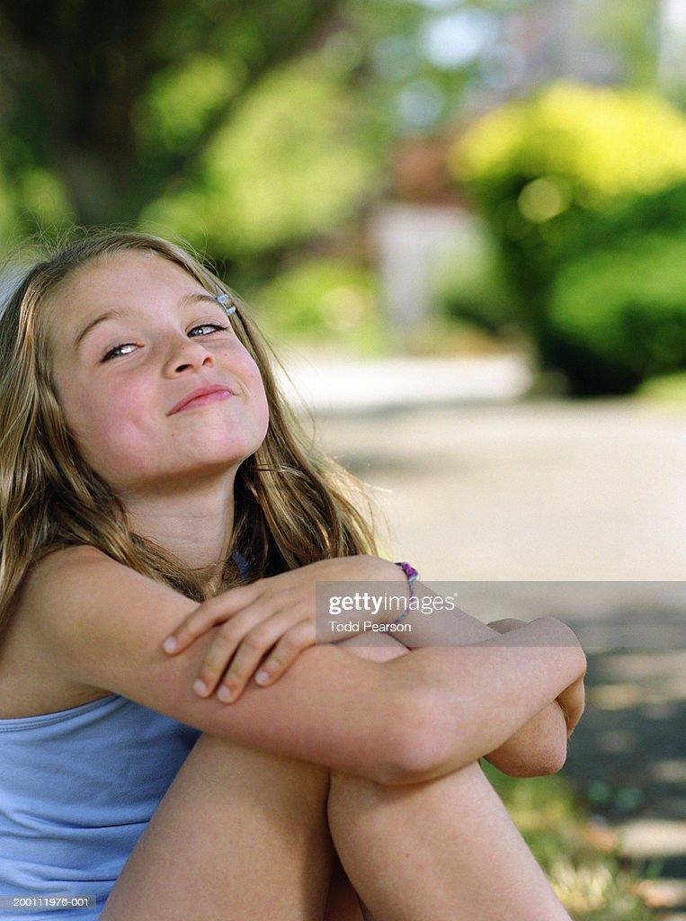 Girl (7-9) sitting on lawn (focus on girl) : Stock Photo