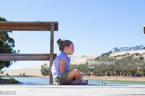 Girl sitting on pier, side view