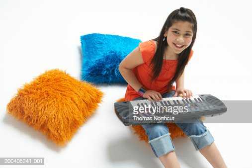 Girl (9-11) sitting on pillow, playing keyboard, elevated view : Stock Photo
