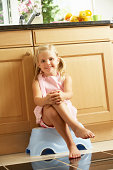 Girl Sitting On Plastic Step In Kitchen