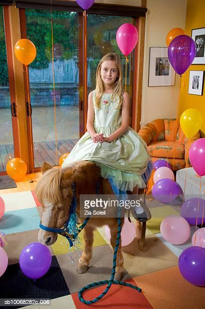 Girl (8-9) sitting on pony in living room, smiling portrait