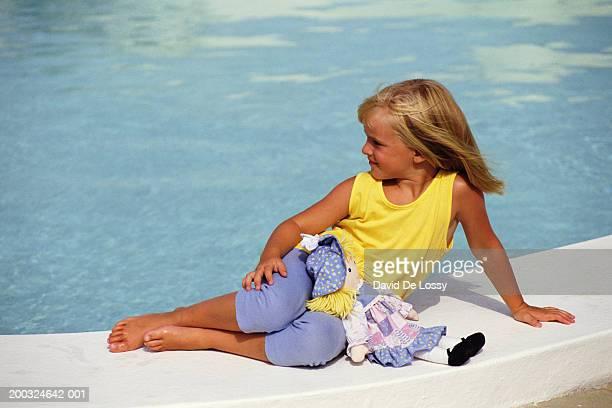 Girl (4-5) sitting on poolside looking away