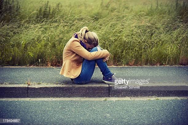 Girl sitting on sidewalk, hiding face