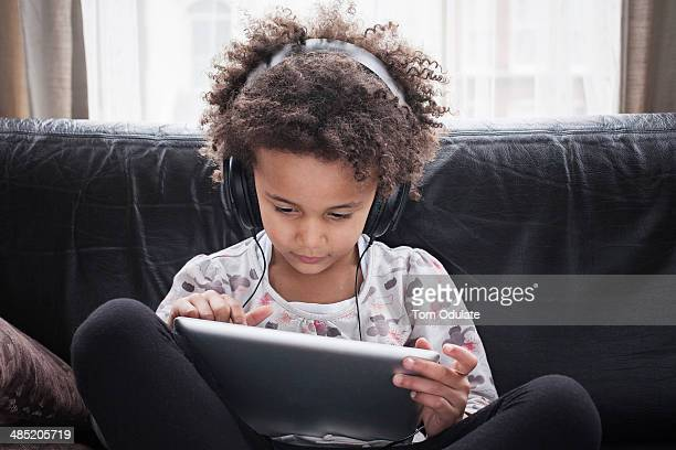 Girl sitting on sofa using digital tablet and headphones