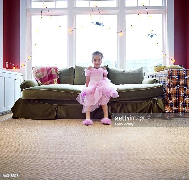 Girl (4-6) sitting on sofa, wearing ballerina costume, portrait