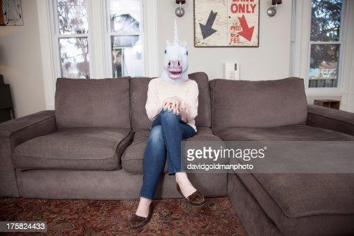 Girl sitting on sofa wearing unicorn head mask : Foto de stock