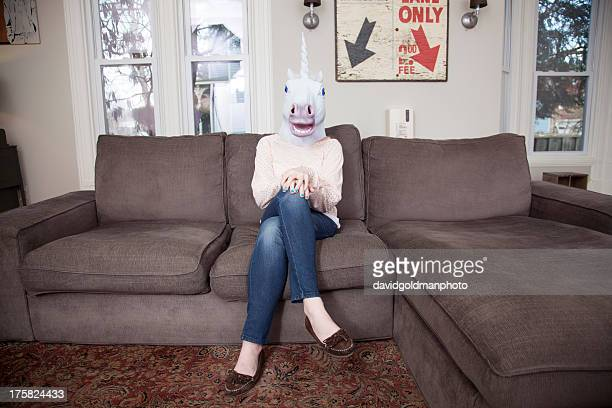 Girl sitting on sofa wearing unicorn head mask
