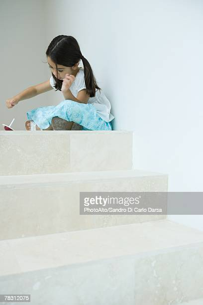 Girl sitting on steps playing with top, low angle view