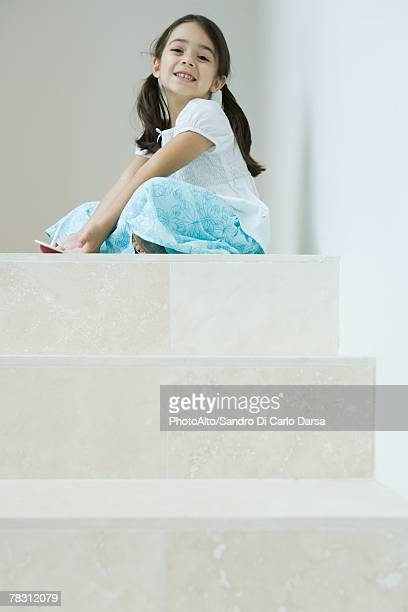 Girl sitting on steps playing with top, smiling at camera, low angle view