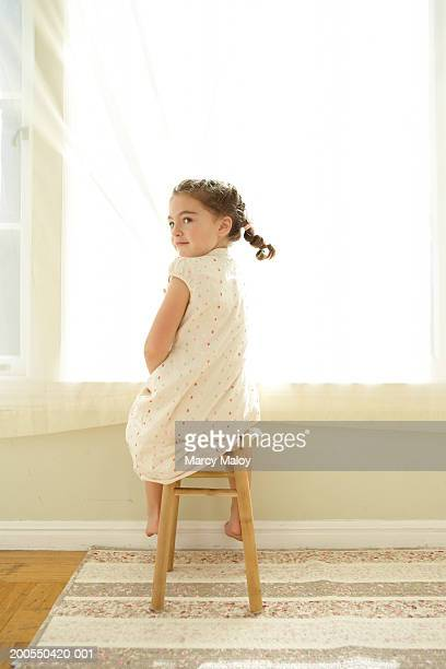 Girl (5-7) sitting on stool, looking over shoulder, rear view