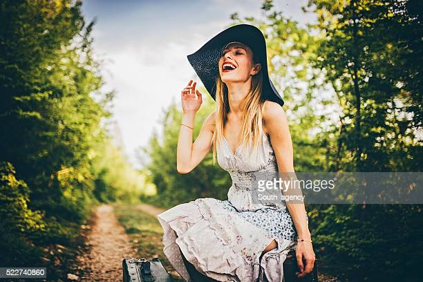 Girl sitting on suitcase and laughing