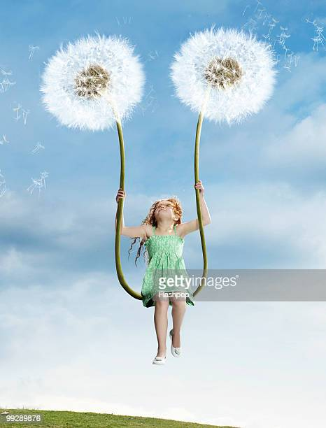 Girl sitting on swing made of dandelions