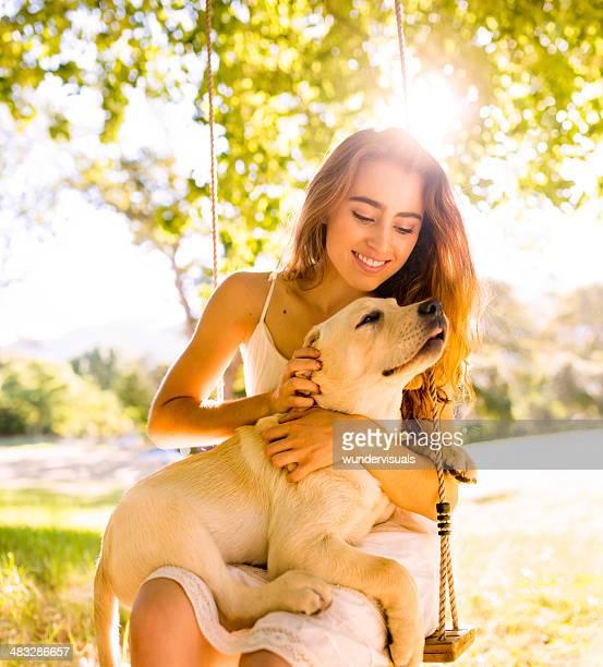 の女の子に座ってスイングに犬