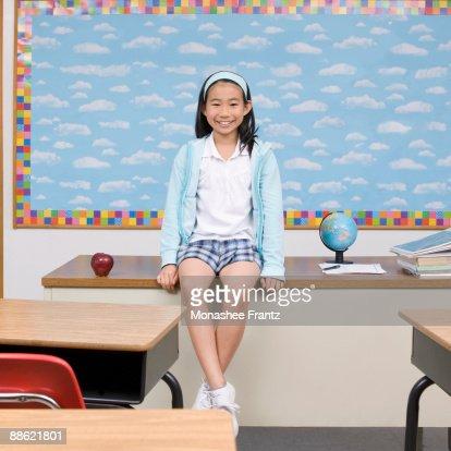 Girl sitting on teachers desk in classroom : Photo