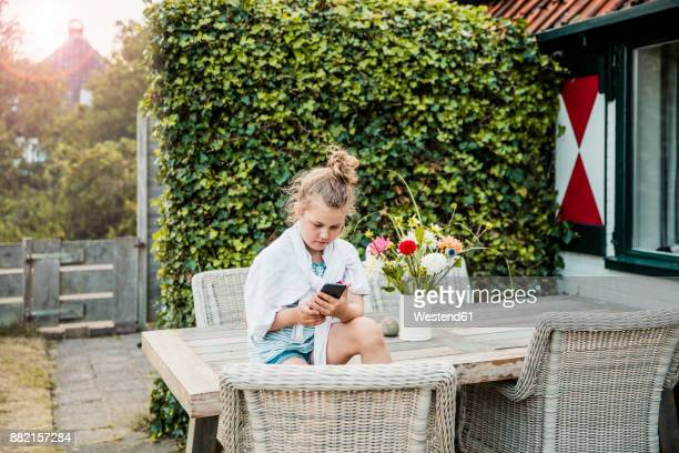 Girl sitting on terrace table using cell phone