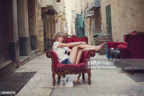 Girl sitting on the armchair on the alley