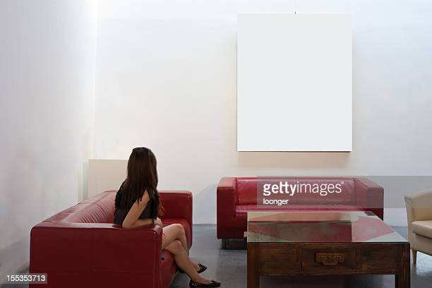 Girl sitting on the couch and watching frame