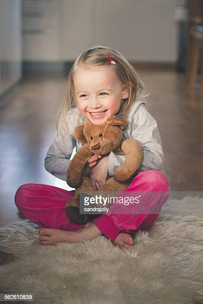 Girl sitting on the floor hugging her teddy bear