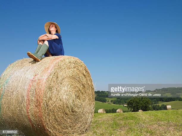 Girl sitting on top of bale of hay
