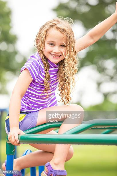 Girl Sitting on Top of Jungle Gym at Playground