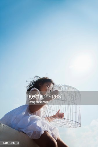 Girl (6-7) sitting on wall with empty birdcage, low angle view : Foto de stock