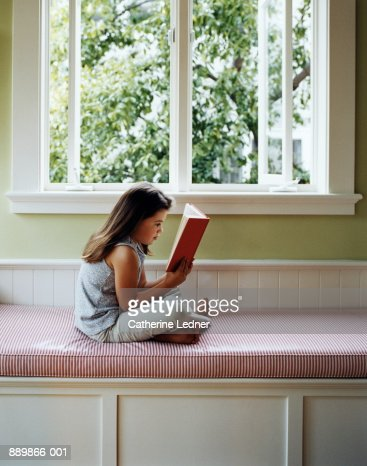 Girl Sitting On Window Seat Reading Book Stock Photo