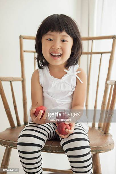 Girl sitting on wooden chair holding apples,  portrait