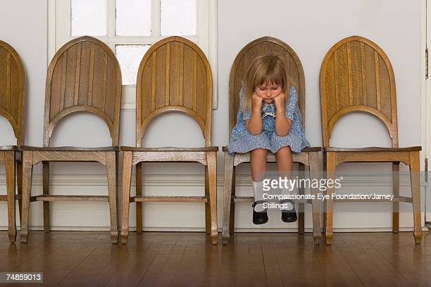Girl (6-7) sitting on wooden chair in corridor