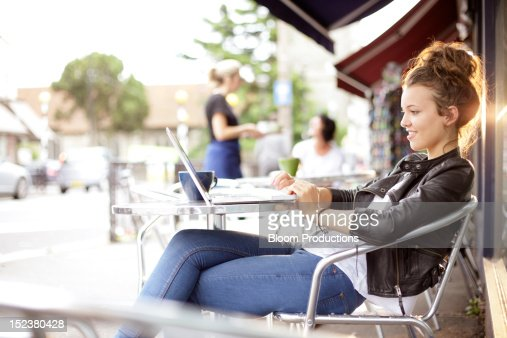 girl sitting outside a cafe using technology : Stock Photo