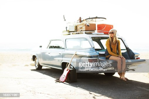 A girl sitting the tailgate of a classic car.