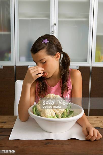 Girl sitting with cauliflower, holding her nose.