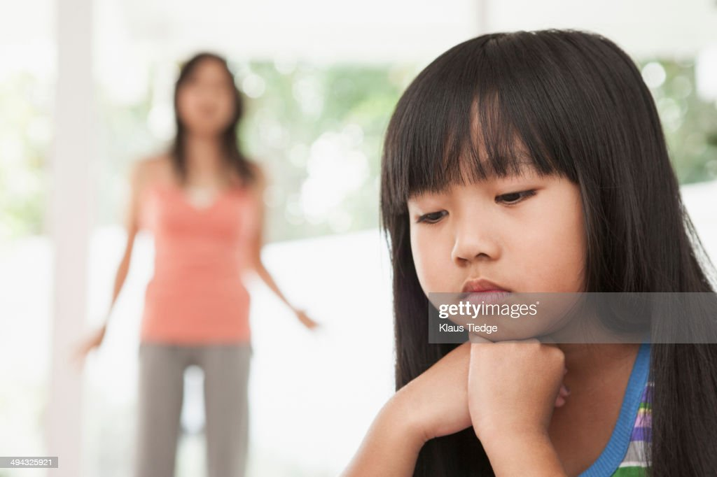 Girl sitting with chin in hands : Stock Photo