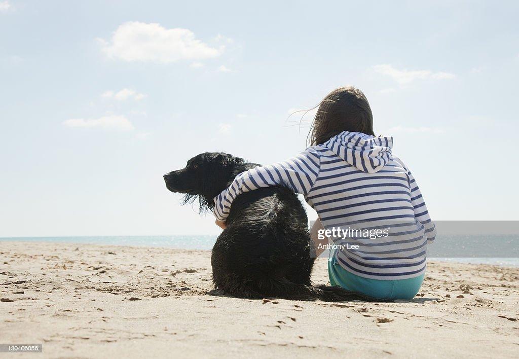 Girl sitting with dog on beach : Stockfoto