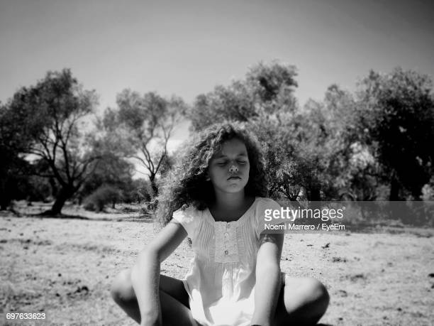 Girl Sitting With Eyes Closed On Field Against Sky