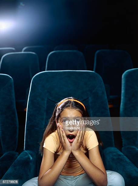 Girl sitting with her head in hands in a movie theatre