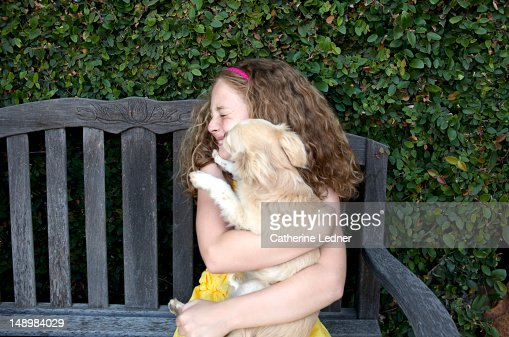 Girl sitting with kissing dog. : Stock Photo