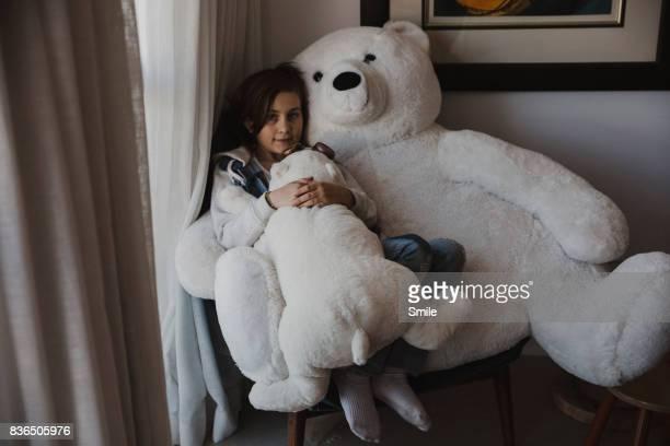 Girl sitting with large polar teddy bears
