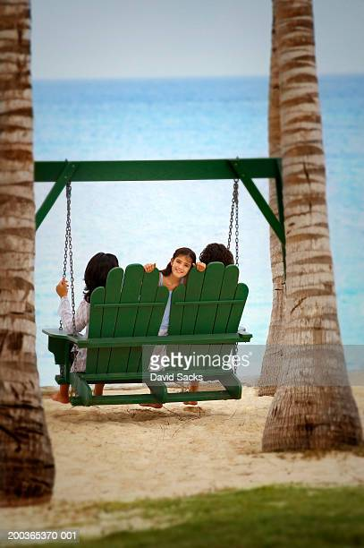 Girl (6-8) sitting with parents on swing chair, portrait, rear view